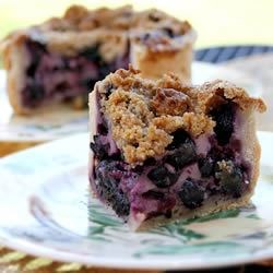 Creamy Blueberry Pie Recipe - A sweet, custardy sour cream mixture is spooned over fresh blueberries, topped with a sweet buttery crumble, and baked. If desired, garnish with mint sprigs and additional blueberries.