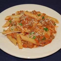 Penne with Spicy Vodka Tomato Cream Sauce Recipe - Hearty Italian sausages sauteed with garlic and red pepper flakes are simmered with tomatoes and cooked with vodka and cream to make a rich, spicy sauce. Toss with penne and fresh parsley to serve.
