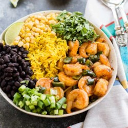 Chipotle Shrimp and Rice Bowl Recipe - Shrimp with poblano peppers in chipotle adobo sauce are served atop seasoned yellow rice with chopped green onions, cilantro, and lime wedges.