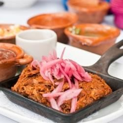 Authentic Cochinita Pibil (Spicy Mexican Pulled Pork) Recipe - Pork shoulder slow cooks in a sauce of orange juice, guajillo chile peppers, vinegar, garlic, and achiote paste to deliver traditional Mexican flavor with relatively low effort.