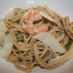 Champagne Shrimp and Pasta Recipe - Toss hot, cooked pasta with cream and parsley, spoon the rich shrimp with champagne and cream sauce over the pasta, and top with Parmesan cheese for a meal made for a king. Simple to make, especially if you purchase shrimp that has already been peeled.