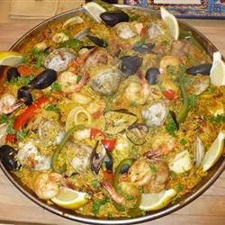 Maria's Paella Recipe - This delicious seafood paella has been made by my family in Catalonia, Spain for many generations. Chicken, shrimp, calamari, clams, and scallops are cooked to perfection in saffron-flavored rice.