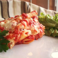 Inside-Out Manicotti Recipe - Think of this as manicotti unbound. Cooked ziti is layered with a creamy blend of ricotta and mozzarella cheeses, enriched with egg and fragrant with nutmeg. A full-flavored tomato and basil sauce blankets the layers. Bake until bubbly and serve!