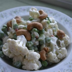 Pea and Cauliflower Salad Recipe - Pretty white cauliflower with three shades of green --peas, olives, and celery-- is mixed with a creamy yogurt dressing, and topped with crunchy cashews.
