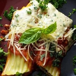 Beefy Manicotti Recipe - This is a very filling, easy to make manicotti dish my whole family loves- including my picky 2 year old!  Manicotti shells are filled with a beefy stuffing before being slathered with tomato sauce and baked.