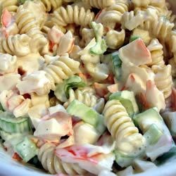 Seafood Pasta Salad Recipe - Rainbow pasta dotted with green peas, crunchy bits of celery, and imitation crabmeat is wrapped in a creamy dressing with a touch of sweetness.