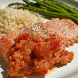 Salmon with Tomatoes Recipe - The natural deliciousness of salmon is enhanced with a delicate blend of spices, a little butter, and Parmesan cheese.