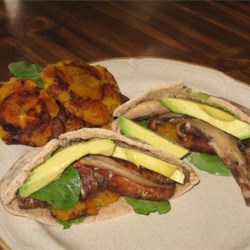Mushroom Patacone Pita Recipe - Warmed pita pockets are stuffed with fried plantains, sliced mushrooms, avocado, and arugula.