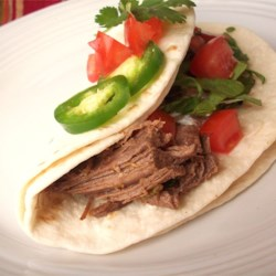Ronaldo's Beef Carnitas Recipe - Chuck roast is wrapped in foil with Mexican-style seasonings, and cooked at low temperature until it is tender and shreds easily. This is served in flour tortillas. Leftovers freeze well.