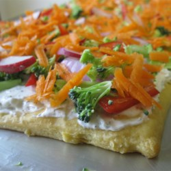 Veggie Pizza Recipe and Video - Crescent-roll dough, baked in a log, becomes the perch for a ranch-dressing spread and fresh, crunchy vegetables.