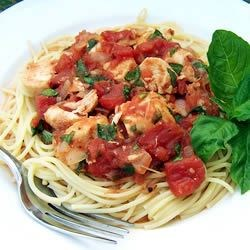 Basil Chicken over Angel Hair Recipe - Cubed chicken breast is simmered in a peppery tomato-basil sauce and tossed with fine strands of angel hair pasta.