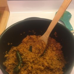 Maria's Mexican Rice Recipe - A serrano pepper kept whole adds flavor without bringing heat to this Mexican-style rice dish with tomato and onion.