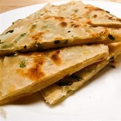 Pan-Fried Chinese Pancakes Recipe - A savory dough is sprinkled with green onions and sesame oil, coiled into a round, then rolled out into flatbreads and pan-fried. Serve with hot and sour sauce or your favorite Chinese sauce for dipping.