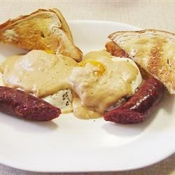 Cajun-Style Eggs Benedict Recipe - Forget the English muffins, Canadian bacon, poaching eggs, and harassing Hollandaise sauce.  This biscuit, egg, and andouille sausage breakfast topped with a simple Mornay sauce is terrific.