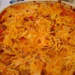 Beef Taco Bake Recipe - Ground beef, spicy tomato sauce, tortillas and cheese are layered and baked for a hearty one-dish meal.