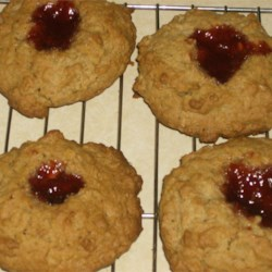 Oatmeal Thumbprints Recipe - These oatmeal cookies with almonds have a raspberry filling for a delightful fruit-and-nut blend.
