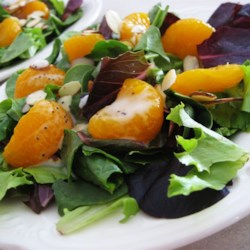 Spinach Salad with Poppy Seed Dressing Recipe - A colorful mix of baby greens, mandarin oranges, and almonds is topped with a sweet and tangy poppy seed dressing.