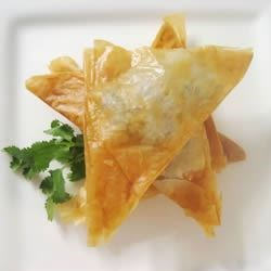 Phyllo Turnovers with Shrimp and Ricotta Filling Recipe - A creamy filling of ricotta cheese and shrimp mixed with green peppers, celery, and green onions and folded into bite-sized phyllo triangles is always a popular party appetizer.