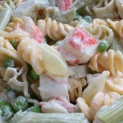 Colorful Seafood Pasta Salad Recipe - Pretty rainbow pasta is dotted with green peas, crunchy bits of celery and imitation crabmeat, and wrapped in a creamy dressing with a touch of sweetness for a cool, colorful salad.