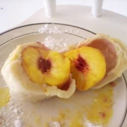 Peach Dumplings Recipe - My dad made the best peach dumplings. Each peach was wrapped in homemade potato dough and dropped into boiling water to cook. To serve, cut them up and sprinkle them with crushed vanilla wafers, sugar, and melted butter.