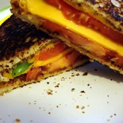 Grilled Cheese with Tomato, Peppers and Basil Recipe - Classic grilled cheese sandwiches with a kick.  Delicious!  These are great with a bowl of tomato soup with a little basil added.