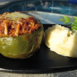 Kelsey's Favorite Stuffed Green Peppers Recipe - Green peppers stuffed with a mixture of ground beef, rice and onion, seasoned with garlic powder and held together with tomato sauce are topped with shredded mozzarella cheese and baked.