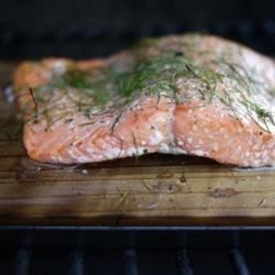 Cedar Plank-Grilled Salmon with Garlic, Lemon and Dill Recipe - Cooking a lemon and dill seasoned whole salmon fillet on a smoldering cedar plank adds a touch of smoke to a beautiful fish!