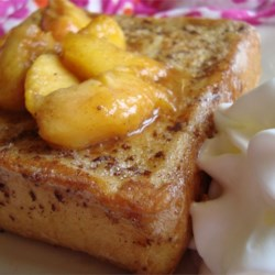 Mascarpone Stuffed French Toast with Peaches Recipe - Lemon zest and mascarpone are stuffed into thick white bread slices, dipped in batter, pan fried, and smothered in fresh peach sauce. This recipe is great for breakfast and fancy enough for dessert.