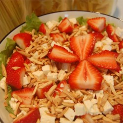 Strawberry and Feta Salad Recipe - A lively mixture of lettuce, strawberries, almonds, and feta is tossed with a tangy oil and vinegar dressing!