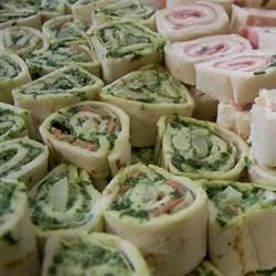 Spinach Roll-Ups Recipe - The popular recipe for sour-cream-based spinach dip turns up in a tortilla here--rolled and sliced into bite-size pinwheels.