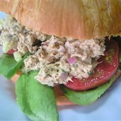 Carrie's Garlic Pesto Tuna Salad Sandwiches Recipe - I love creating new variations on tuna sandwiches. This one is made with basil pesto, and served on rye bread with slices of tomato and leaves of lettuce. I made this for my husband's lunch the other day, and he wanted them again for dinner that night!