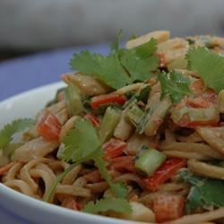 Chicken Noodle Salad with Peanut-Ginger Dressing Recipe - Asian flavors star in this chicken-linguine pasta salad that tosses julienned carrots, celery, green onions, and cilantro with a zesty ginger-peanut-garlic seasoned dressing.