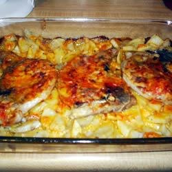 Scalloped Potatoes and Pork Chops Recipe - Cheesy potatoes and onions with seasoned pork chops on the top.