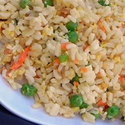 Fried Rice Restaurant Style Recipe - A great way to use up leftover rice, this quick fried rice cooks up with frozen peas, baby carrots, eggs, and soy and sesame sauces.