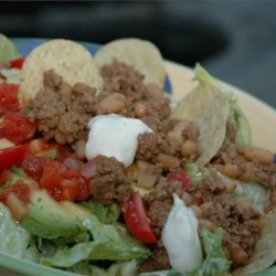 Joy's Taco Salad Recipe - Everything that you like to put in or on your favorite taco is in this incredibly tasty salad  - jalapeno peppers, ground beef, beans, cheese, lettuce, green onion. The dressing is low fat and spiked with taco seasoning mix.