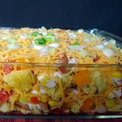 Mexican Cornbread Salad Recipe - This layered salad is made with green chile cornbread, pinto beans, peppers, corn, bacon bits, tomatoes, and cheese. It's then chilled for two hours to allow the flavors to blend.
