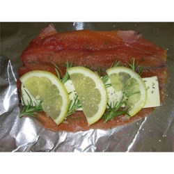 Grilled Montana Trout Recipe - Trout is stuffed with lemon, garlic and herbs before being wrapped in aluminum foil and cooked over the coals of the campfire or on your grill.