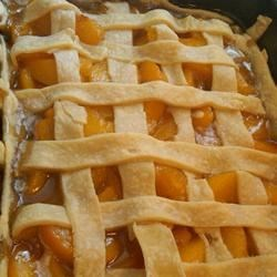 Old Fashioned Peach Cobbler Recipe - Flaky pastry enclosing peaches flavored with lemon and orange juice and spiced with nutmeg and cinnamon.