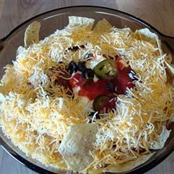El Dorado Beef Casserole Recipe - This layered casserole with ground beef, black olives, sour cream, ricotta cheese and green chiles is baked, then garnished with whole tortilla chips.