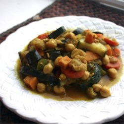 Marrakesh Vegetable Curry Recipe - This curry is full of veggies: sweet potato, eggplant, spinach, zucchini, red and green bell peppers, carrots, and onion. It's mixed with blanched almonds, chickpeas, raisins, and spices. Serve with brown rice or couscous.