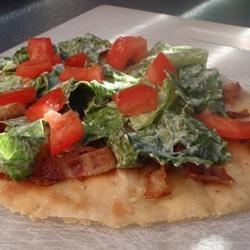 BLT Pizza Recipe - A classic favorite is reincarnated as a pizza. Bacon and tomatoes are baked onto a pizza crust then topped with a seasoned shredded lettuce to make an unforgettably fun meal.
