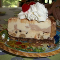 Chocolate Chip Cookie Ice Cream Cake Recipe and Video - Your favorite ice cream flavors in a cookie crust, topped with whipped cream, fudge and cherries.