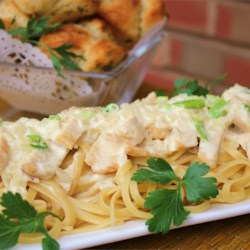 Creamy Chicken on Linguine Recipe - Tender strips of chicken browned in oil, butter and garlic are arranged over hot pasta and topped with a sumptuous sauce of cream, milk, onions, scallions and Parmesan cheese.