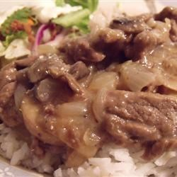 Simply Elegant Steak and Rice Recipe - Round steak is cut into strips and sauteed with onions, then simmered for an hour with mushroom soup, sliced mushrooms, and sherry, and served over rice.