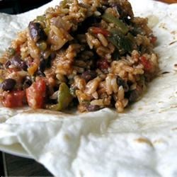 Barbeque Seitan and Black Bean Burritos Recipe - Cooked rice and barbecue sauce are combined with a heavenly mixture of cooked seitan, onions, scallions and hot chile peppers. The filling is spooned into flour tortilla, and when all ten are wrapped and ready, they're baked with additional barbecue sauce.
