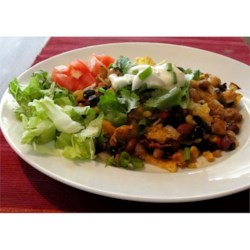 Funky Enchilada Casserole Recipe - Chicken breasts, spices, black beans, kidney beans, and colorful bell peppers are baked with corn tortillas and topped with cheese in this great quick casserole. Serve with sour cream, hot sauce, diced tomatoes, and guacamole, if desired.