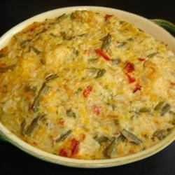 Chicken and Rice Casserole II Recipe - This hearty casserole is made with chicken, cooked rice, and a homemade Cheddar cheese sauce. To save time, you may use leftover cooked chicken.