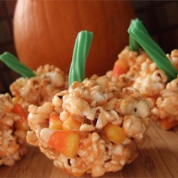 Halloween Popcorn Pumpkins Recipe - Popcorn balls are colored orange and made to look like pumpkins. These are a fun Halloween treat for kid and adult parties. Very versatile!