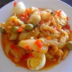 Bacalao a la Vizcaina (Basque Style Codfish Stew) Recipe - Soaked salt cod is layered with potatoes, eggs, golden raisins, capers, and roasted red peppers, then simmered in a white wine-tomato sauce.