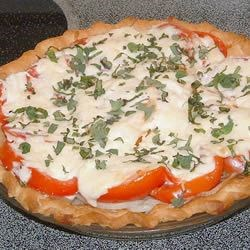 Fresh Tomato Pie Recipe - This savory layered pie is a great way to use up extra summer tomatoes--and it's delicious warm or cold. Layers of sliced onion and tomato are topped with Parmesan and mozzarella cheeses. The pie is baked until golden brown, and then garnished with chopped fresh herbs.